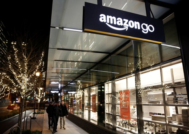 People walk by the Amazon Go brick-and-mortar grocery store without lines or checkout counters, in Seattle Washington, U.S. December 5, 2016. REUTERS/Jason Redmond