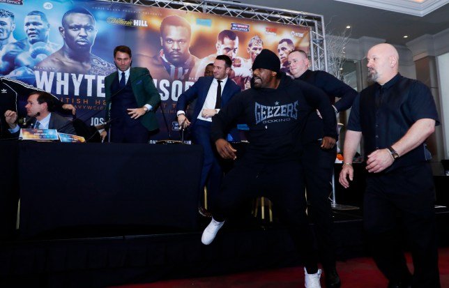 Boxing Britain - Dillian Whyte & Dereck Chisora Head-to-Head Press Conference - Radisson Hotel, Manchester - 7/12/16 Sky Sports' Adam Smith, promoter Eddie Hearn and promoter Kalle Sauerland look on as Dereck Chisora throws a table towards Dillian Whyte during the press conference Action Images via Reuters / Jason Cairnduff Livepic EDITORIAL USE ONLY.