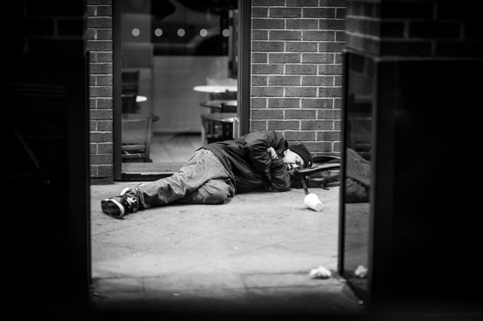 LONDON, ENGLAND - OCTOBER 27: (SUN NEWSPAPER OUT. MANDATORY CREDIT PHOTO BY DAVE J. HOGAN GETTY IMAGES REQUIRED. EDITORS NOTE: Image was shot in black and white. Color version not available.) A homeless man sleeps on the street on October 27, 2014 in London, England. (Photo by Dave J Hogan/Getty Images)