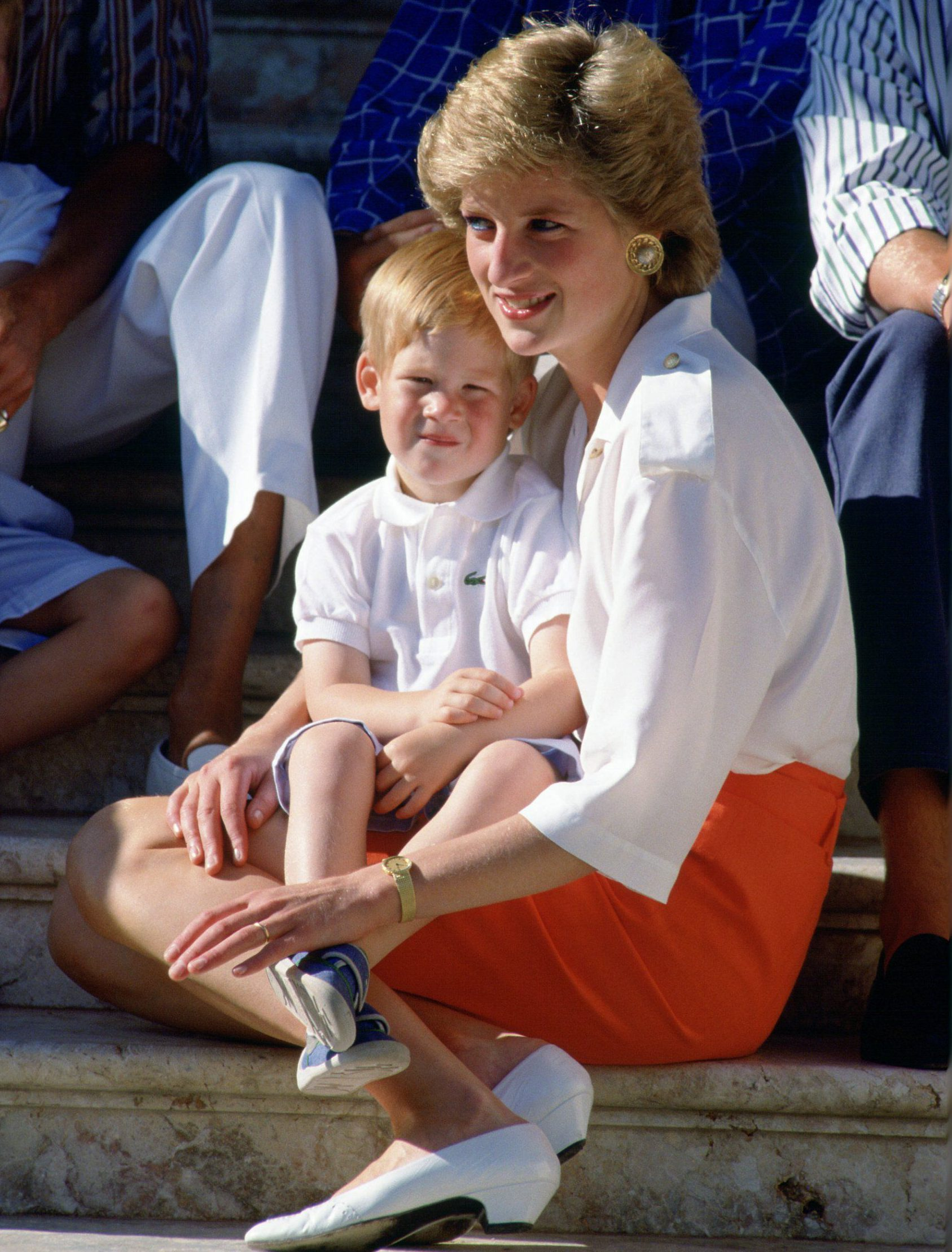 PALMA, SPAIN - AUGUST 13:  Diana, Princess Of Wales, Sitting On The Steps Of The Marivent Palace With Her Son, Prince Harry, Sitting On Her Lap At A Photocall During Their Summer Holiday. Prince Harry's T-shirt Is By Fashion Designer Lacoste.  (Photo by Tim Graham/Getty Images)