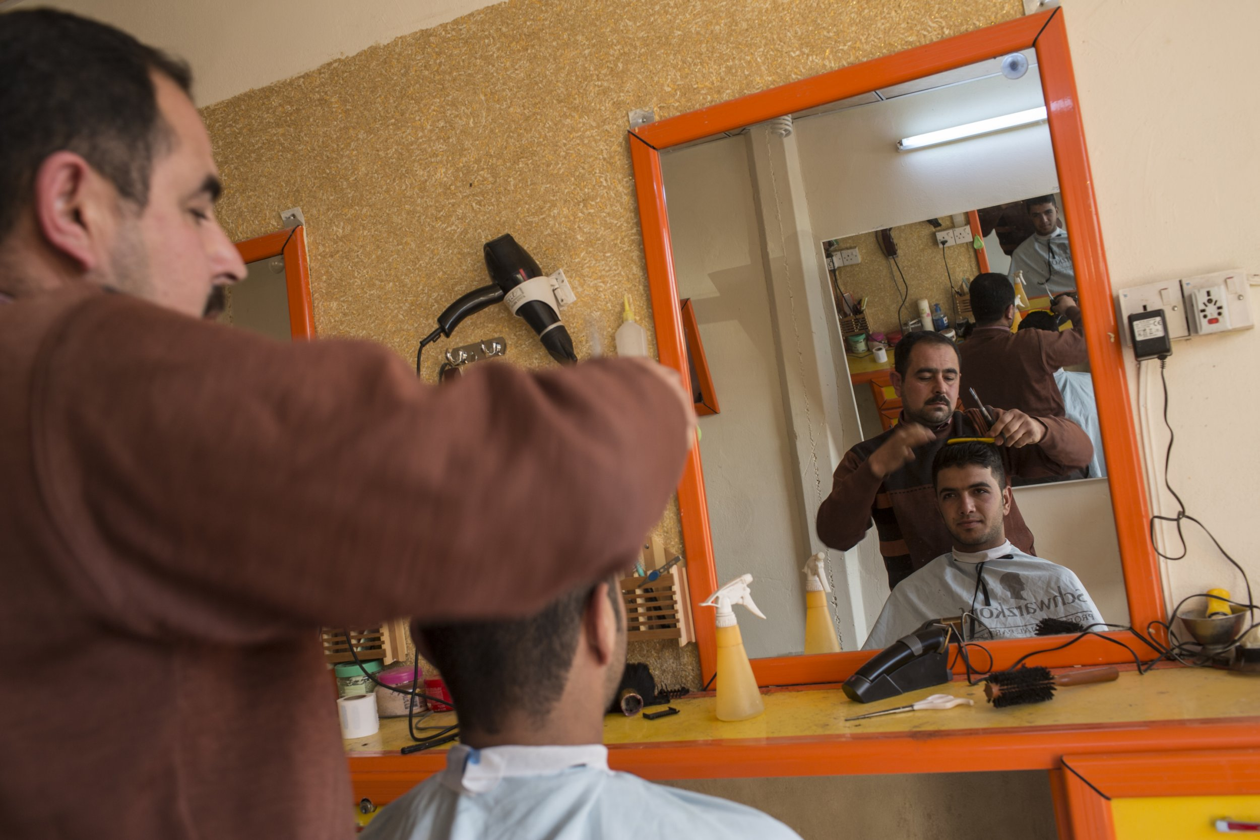 """Barber Saed Ahmed, 38, in his hair salon in Jalawla, Iraq. Saed was given a loan by Oxfam to repair his """"golden scissors"""" salon after it was damaged during the ISIS occupation of Jalawla.nThe town was was controlled by ISIS between August and November 2014. Oxfam has been helping business owners get back on their feet through small loans and paying people to undertake works to improve the town."""