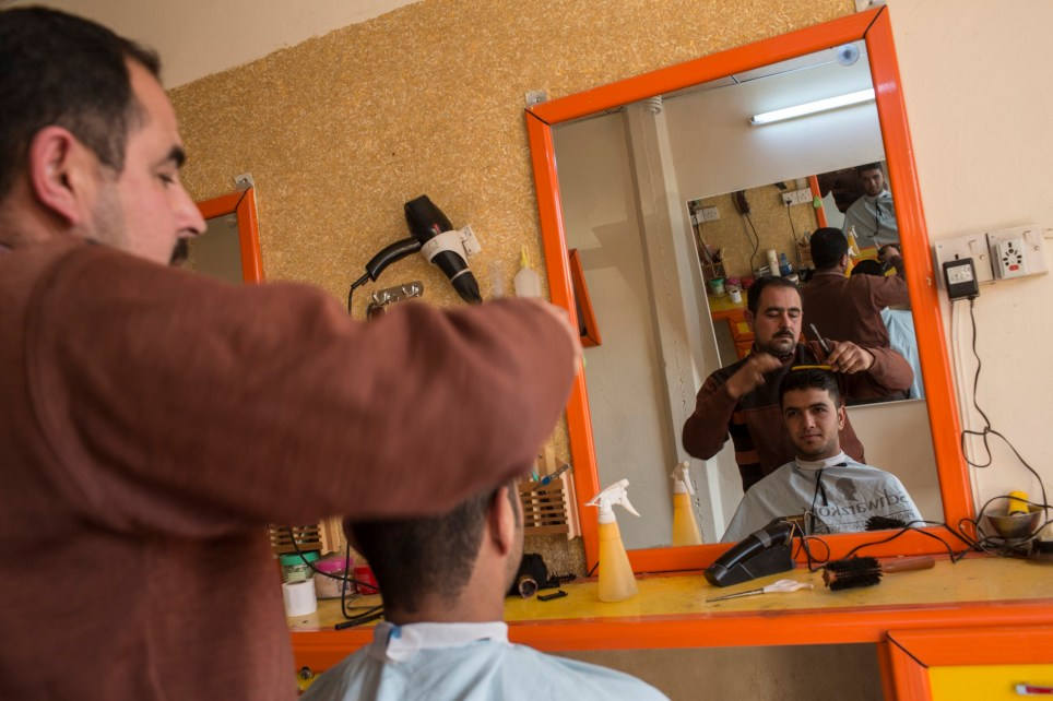 "Barber Saed Ahmed, 38, in his hair salon in Jalawla, Iraq. Saed was given a loan by Oxfam to repair his ""golden scissors"" salon after it was damaged during the ISIS occupation of Jalawla.nThe town was was controlled by ISIS between August and November 2014. Oxfam has been helping business owners get back on their feet through small loans and paying people to undertake works to improve the town."