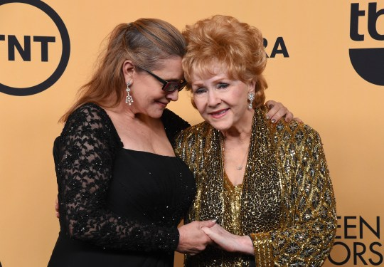 LOS ANGELES, CA - JANUARY 25: Actress Carrie Fisher (L) and honoree Debbie Reynolds pose in the press room at the 21st Annual Screen Actors Guild Awards at The Shrine Auditorium on January 25, 2015 in Los Angeles, California. (Photo by Steve Granitz/WireImage)