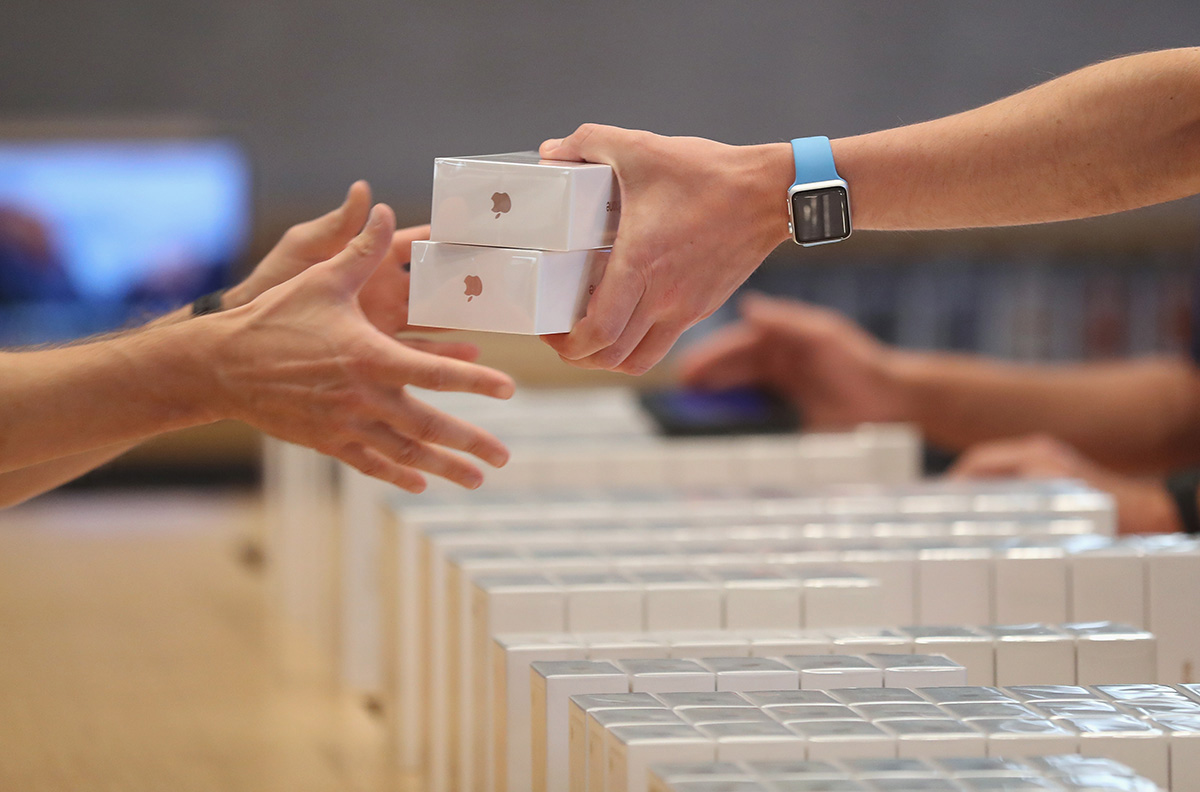 An Apple employee hands over Apple iPhone 7 phones on the first day of sales of the new phone (Picture: Getty Images)