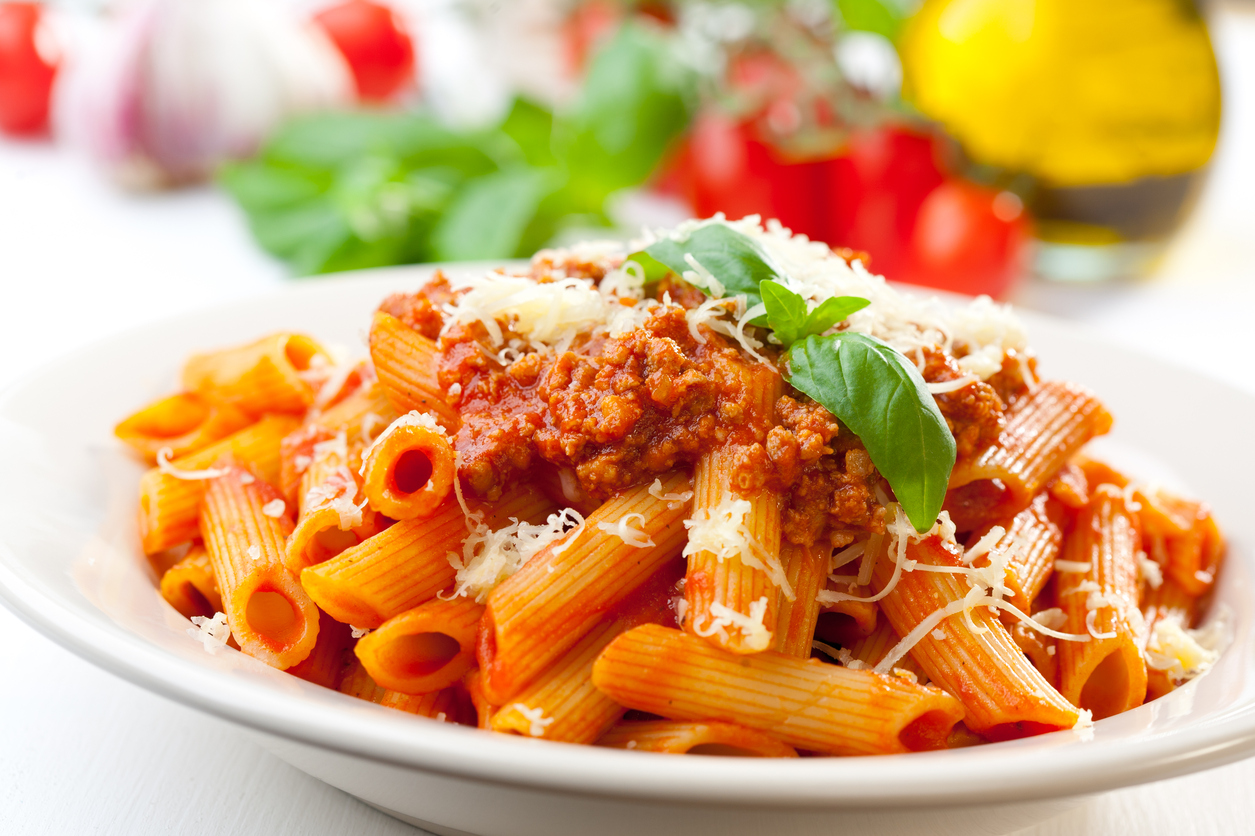 Plate of penne bolognese with ingredients in the background
