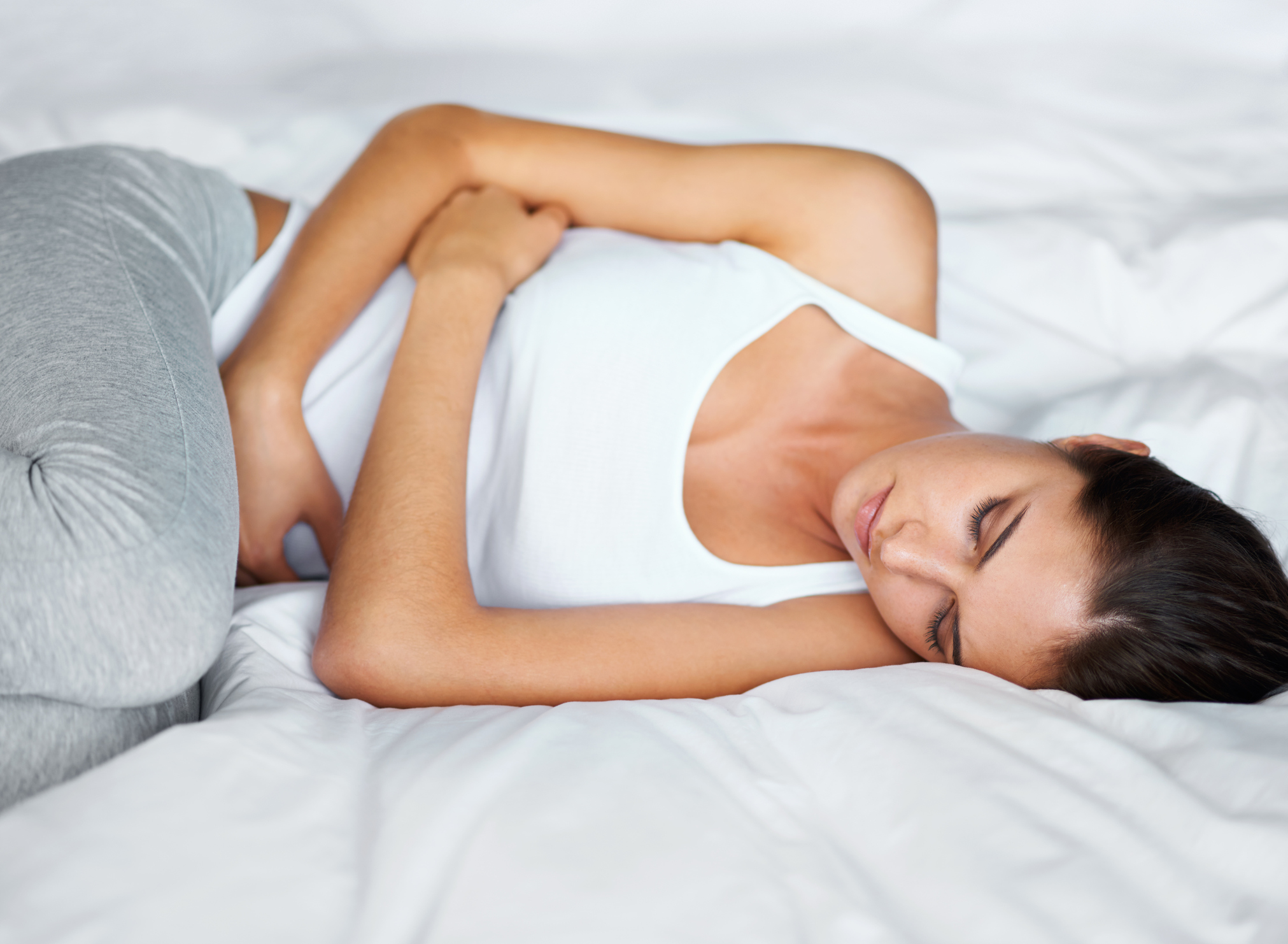 Shot of an attractive young woman lying in bed with cramps