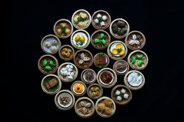 Overhead top-down image of a large variety of dimsum dishes in bamboo pots arranged in a circle formation against plain black background.