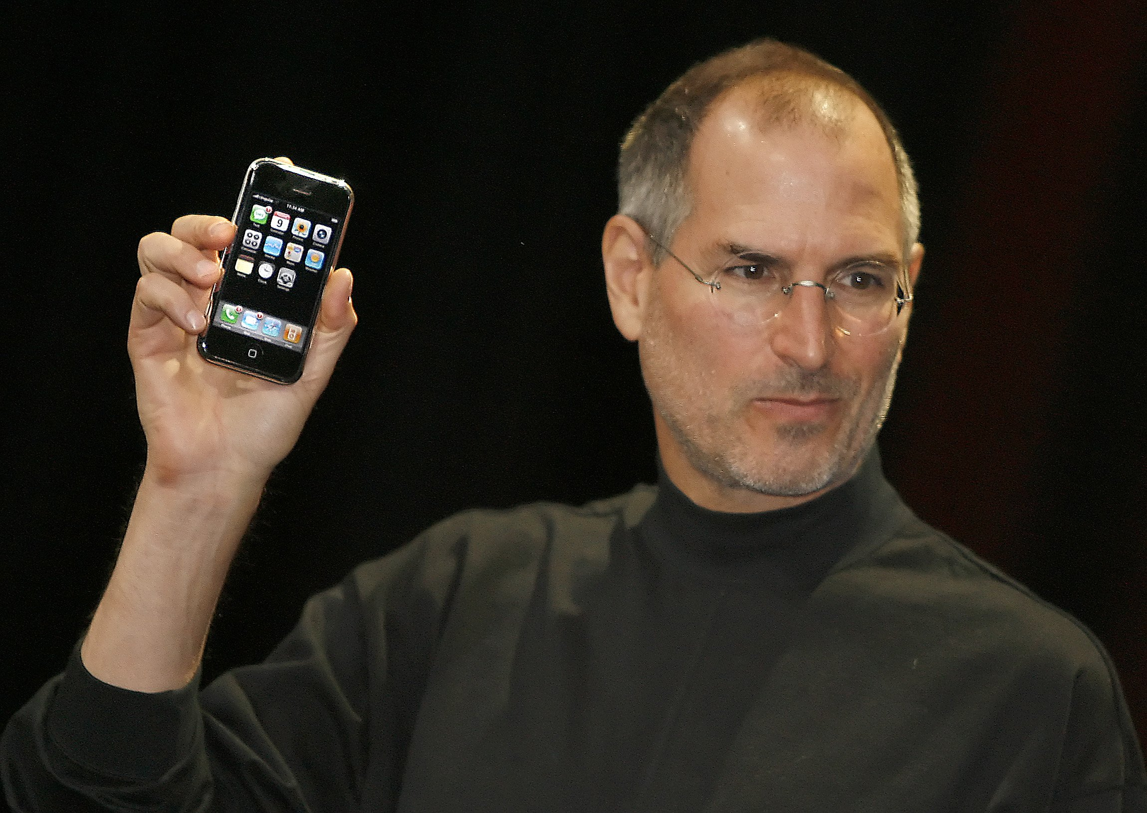 (FILES) This file photo taken on January 9, 2007 at the Macworld Conference in San Francisco, California shows Apple chief executive Steve Jobs unveiling the iPhone, an ultra-slim new mobile phone - less than half-an-inch (1.3 centimeters) thick - boasting a phone, Internet capability and an MP3 player as well as featuring a two megapixel digital camera, Jobs said. Apple celebrates on January 9, 2016 the 10th anniversary of the unveiling of the Iphone, the smartphone that revolutionised the technological world. / AFP PHOTO / TONY AVELARTONY AVELAR/AFP/Getty Images