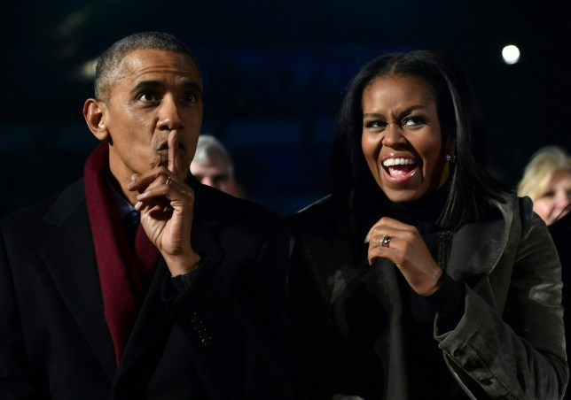 US President Barack Obama and First Lady Michelle Obama react during the National Christmas Tree Lighting on the Ellipse of the National Mall in Washington on December 1, 2016. nThe BCV on Wednesday presented the new bank notes that will be in circulation from December 15, 2016, including a 20,000 bolivars bill. / AFP / Nicholas Kamm (Photo credit should read NICHOLAS KAMM/AFP/Getty Images)