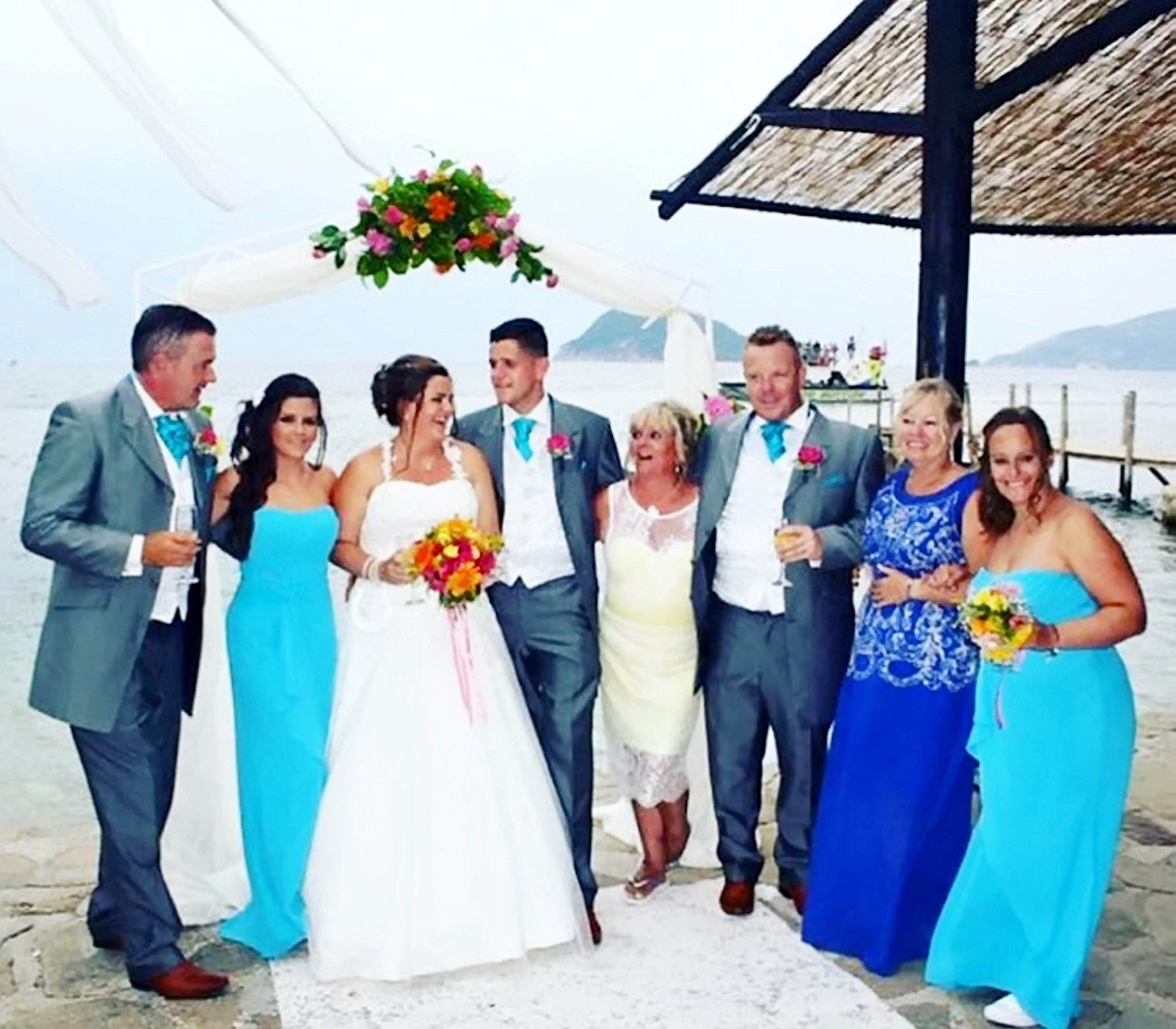 Danielle, 30, and her new husband Mark Woollaston, 38, with their friends and family during their wedding ceremony at the Marelen Hotel in Kalamaki on the Greek island of Zante in August last year. See NTI story NTIWEDDING. A couple are among almost 100 Brits suing a Greek hotel after their dream wedding was ruined when they fell ill with severe stomach bugs - caused by people DEFECATING in the swimming pool. Danielle, 30, and Mark Woollaston (corr), 38, have launched legal action against the Marelen Hotel in Kalamaki on Zante. The pair travelled to the Greek island for two weeks to get married and stayed at the three-star resort with 50 friends and family members in August last year. But their wedding celebrations were ruined because of a severe gastric illness outbreak at the hotel during their stay. The bride, groom and the majority of their guests were then diagnosed with Cryptosporidium, a parasite that causes severe symptoms, on their return to the UK. Danielle and Mark, who live in Sutton Coldfield, West Mids., have now instructed expert personal injury lawyers to investigate the outbreak at the Marelen Hotel.