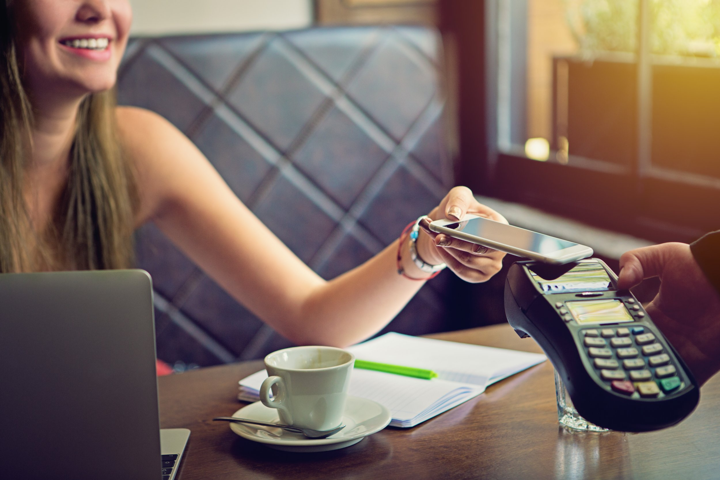 Young woman is paying in the cafe using her mobile phone