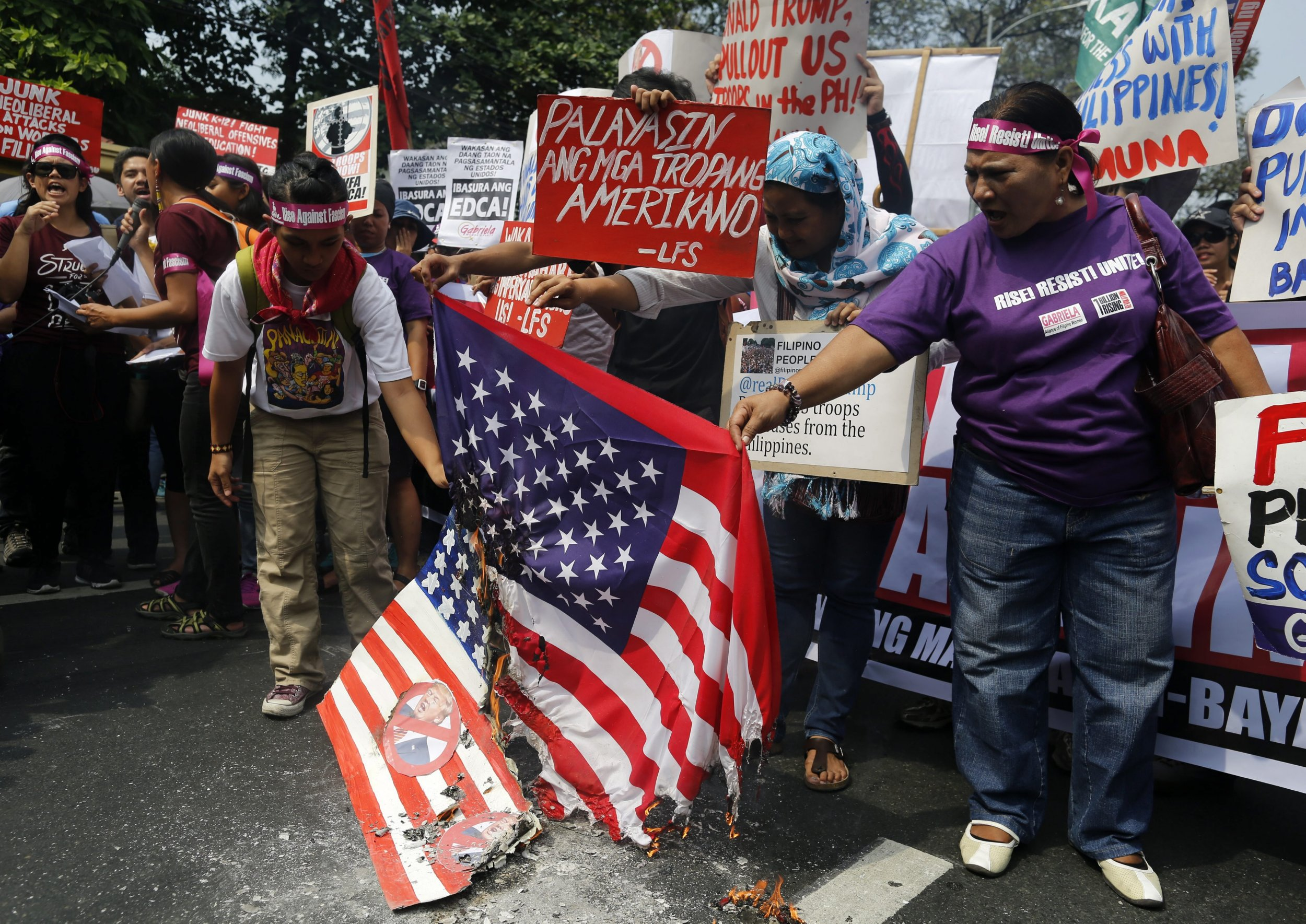 epa05733196 Filipinos and Fil-Americans burn a US flag during a protest rally in front of the US embassy in Manila, Philippines, 20 January 2017, on the eve of President-elect Donald Trump's inauguration as the 45th president of the United States. Filipinos and Filipino-Americans held a protest in front of the US embassy in Manila to denounce the new US president. EPA/FRANCIS R. MALASIG
