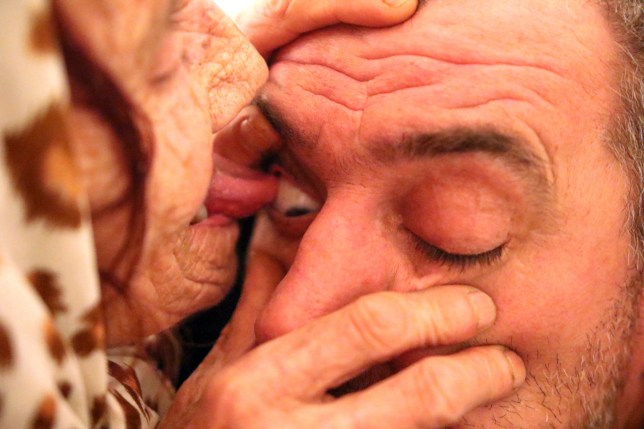 Pic by Armin Durgut/Caters News - (Pictured: Hava Celebic, or as everyone calls her nana Hava treats eyes by licking as she demonstrates here on a male.) - Not content with retirement, an elderly woman has started charging people for her to lick their eyeballs clean. In rural Bosnia and Herzegovina, 80-year-old, Hava Celebic or nana Hava as she is known locally, claims to be the only person in the world who heals with their tongue. The frail old woman uses her tongue to remove pieces of lead, iron, coal, sawdust and glass from eyeballs after sterilising her mouth with alcohol. Patients will raise their eyelid for nana Hava to begin licking in search of a foreign body. SEE CATERS COPY