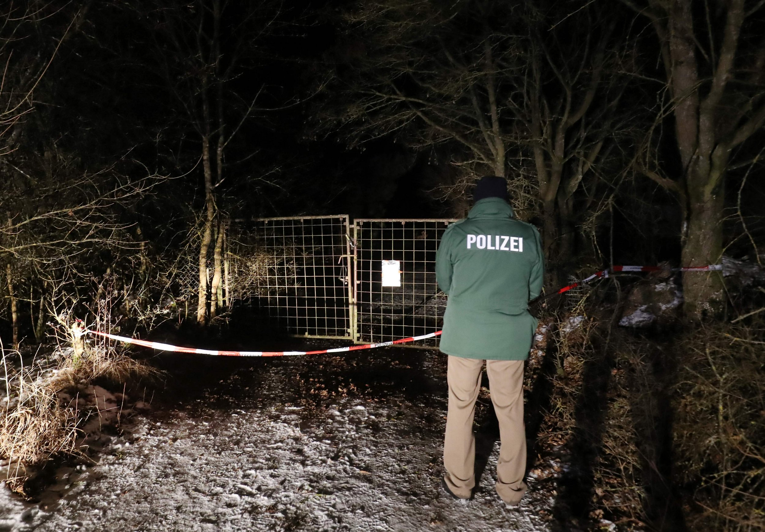 A policeman stands in front of an entrance leading to the site where six teenagers were found dead after holding a party in a garden near Arnstein, southern Germany, on January 29, 2017. The youths were found by the owner of the shed, whose son and daughter were among the victims. / AFP PHOTO / dpa / Daniel Karmann / Germany OUTDANIEL KARMANN/AFP/Getty Images