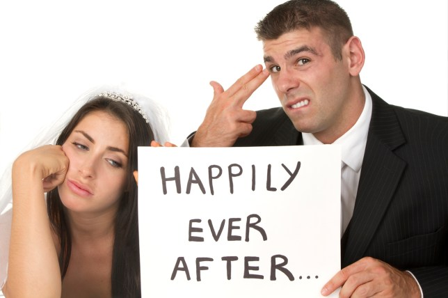 """unhappy bride and groom holding a sarcastic sign that says """"happily ever after..."""" isolated on white background"""