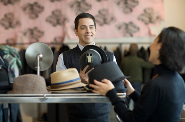 woman buying hat from man