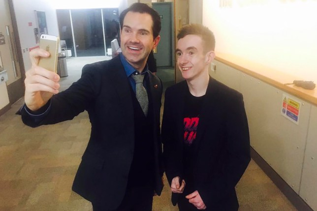 PIC FROM MERCURY PRESS (PICTURED: LEWIS NICKELL WITH JIMMY CARR )  A teenage Tourette's sufferer has revealed footage showing how the syndrome makes him struggle with simple everyday tasks like using a hose - and how he uses it to excuse him from housework. Lewis Nickell, 18, asked his brother to film him using a power hose in the back garden of their home in Bangor, Northern Ireland, to highlight his battle with physical and vocal tics. The youngster blurts out a series of four-letter words and, in one hilarious outburst, proclaims to be 'wetter than a porn star's t*ts' due to the spray from the hose. But Lewis, who developed the condition two years ago, said he was able to see the funny side of his tics - and uses them as an excuse for his 24-year-old brother Stephen to do all the housework. SEE MERCURY COPY