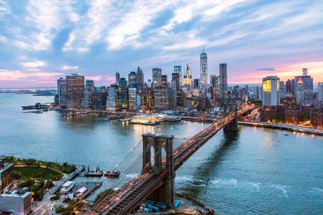 Aerial of lower Manhattan skyline and Brooklyn bridge at dusk, New York, USA