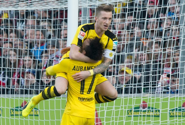 Dortmund's Gabonese forward Pierre-Emerick Aubameyang (R) is congratulated by Dortmund's forward Marco Reus after scoring the 0-2 during the German first division Bundesliga football match between SC Freiburg and Borussia Dortmund in Freiburg, southwestern Germany, on February 25, 2017. / AFP / THOMAS KIENZLE / RESTRICTIONS: DURING MATCH TIME: DFL RULES TO LIMIT THE ONLINE USAGE TO 15 PICTURES PER MATCH AND FORBID IMAGE SEQUENCES TO SIMULATE VIDEO. == RESTRICTED TO EDITORIAL USE == FOR FURTHER QUERIES PLEASE CONTACT DFL DIRECTLY AT + 49 69 650050         (Photo credit should read THOMAS KIENZLE/AFP/Getty Images)