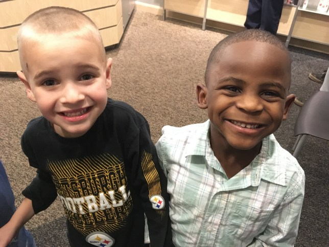 In this Feb. 28, 2017, photo, 5-year-olds Jax, left, and Reddy smile after Jax got a haircut similar to his friend's at the Great Clips in Louisville, Ky. The story about the two boys and their racial harmony went viral online after Jax told his mother that he wanted to get his haircut like Reddy so that their teacher wouldn't be able to tell them apart. (Debbie Weldon via AP)