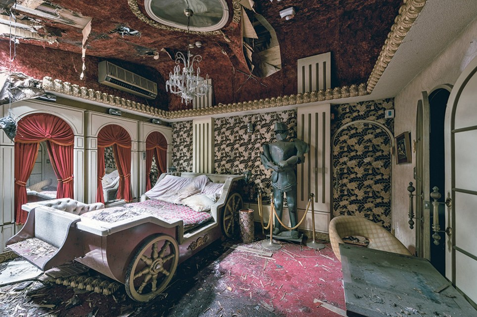 PICS BY BOB THISSEN / CATERS NEWS - (PICTURED: Medievil room with carriage and suit of armour - the Fuurin Motel, once known as a rendevous point for lovers and those conducting extramarital affairs is now supposed to be haunted and scares away locals) - These eerie photographs reveal an abandoned sex motel thought to be haunted by ghosts. Once known as a lovers rendezvous and secret escape for extramarital affairs the empty Fuurin Motel, in Tokyo, Japan, lies perfectly preserved. Guests of the Love Motel rented one of ten quirky themed bedrooms by the hour such as the Medieval suite with a full suit of armour and a carriage-shaped bed. Other room themes include Greek, Traditional Japanese Ryokan and hunting - all with their own dining rooms and bathrooms. Now its believed that ghosts haunt the hotels decaying corridors that closed 17 years ago and its claimed that locals are too scared to enter the property because of the paranormal presence. - SEE CATERS COPY