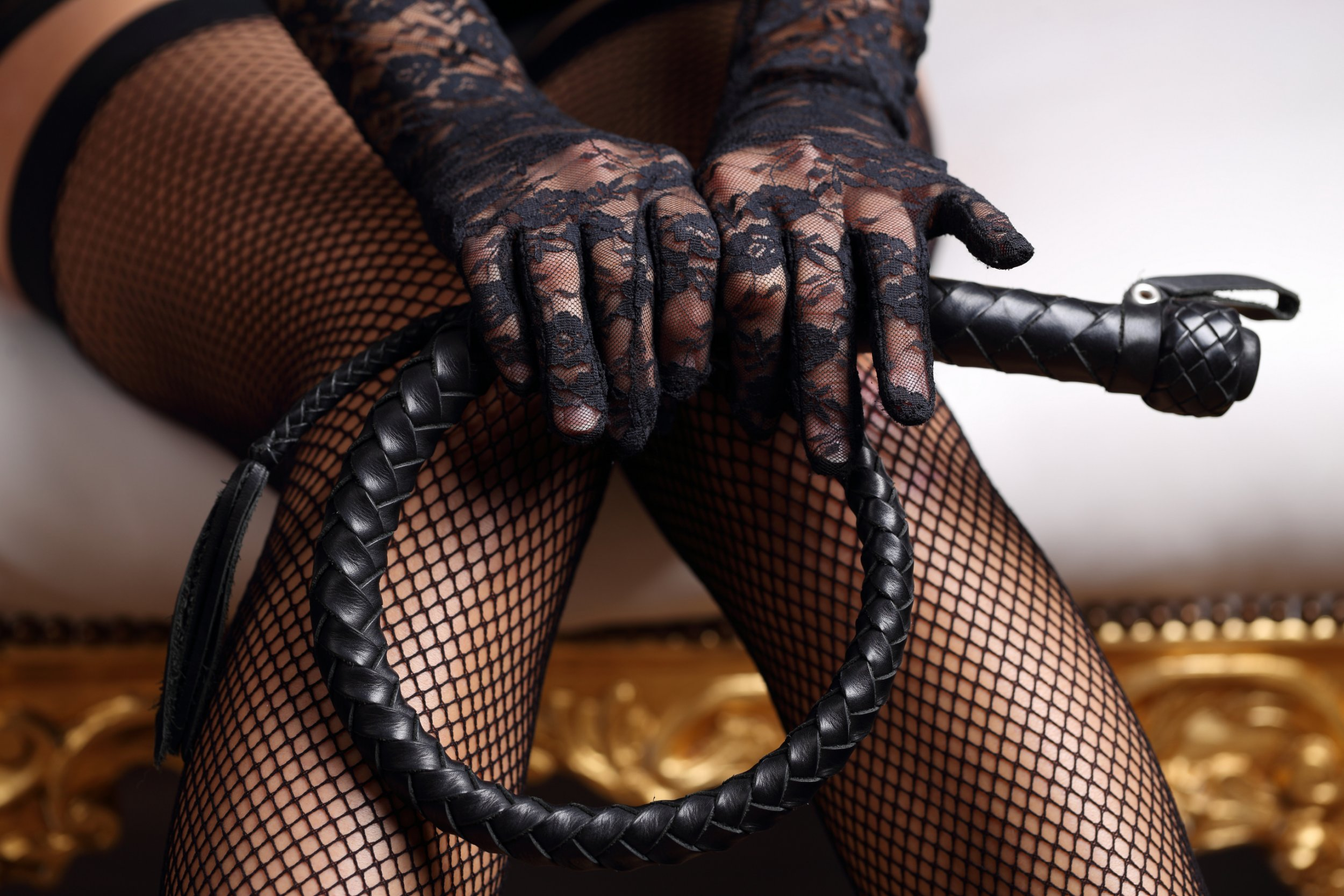 Sensual woman in black lingerie and leather whip; Shutterstock ID 381393499