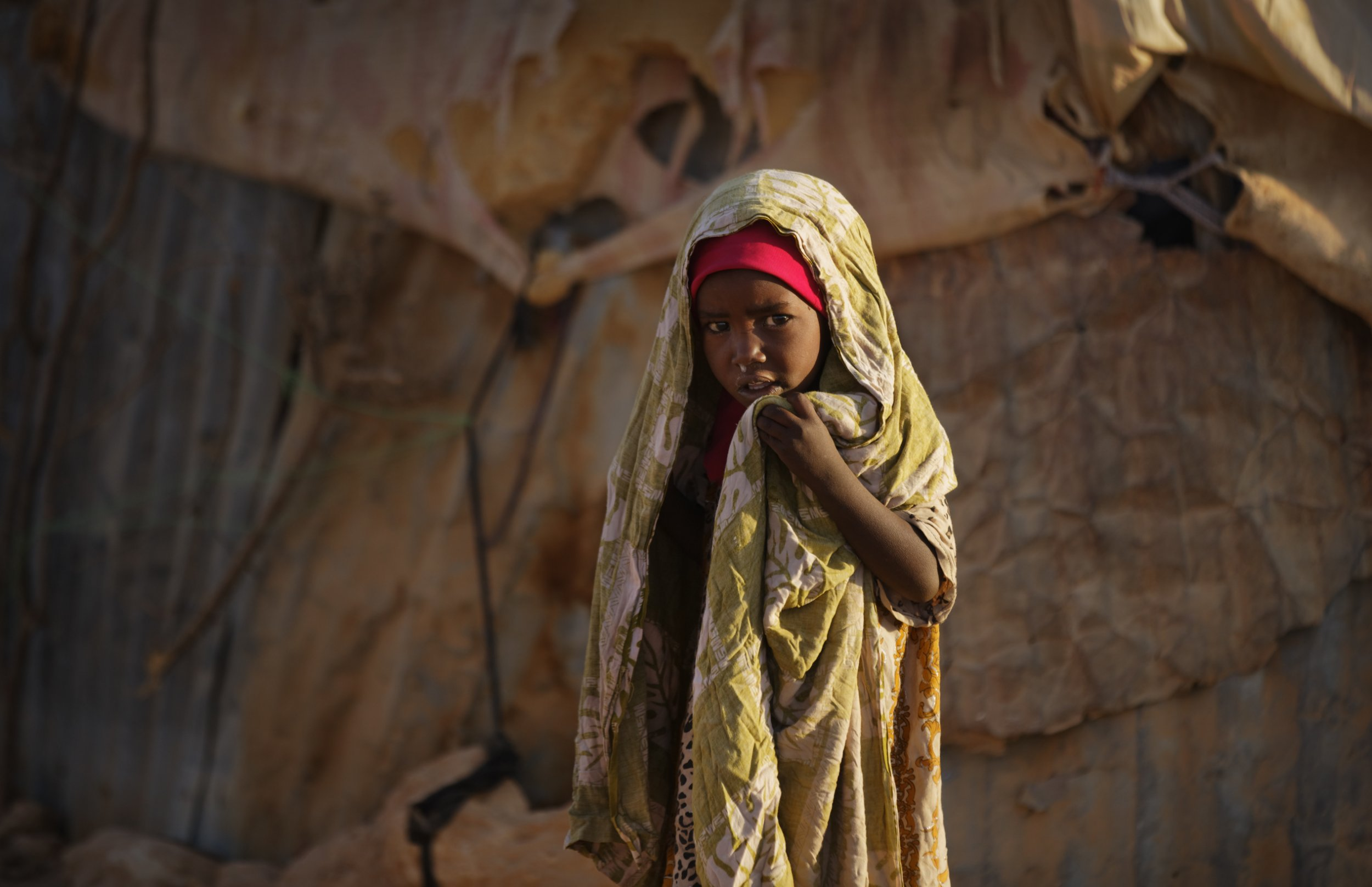 A young Somali girl stands outside her makeshift hut at a camp of people displaced from their homes elsewhere in the country by the drought, shortly after dawn in Qardho, Somalia Thursday, March 9, 2017. Somalia's government has declared the drought a national disaster, and the United Nations estimates that 5 million people in this Horn of Africa nation need aid, amid warnings of a full-blown famine. (AP Photo/Ben Curtis)