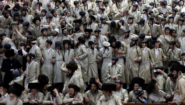 Ultra-Orthodox Jewish men celebrate the Purim holiday in the ultra-orthodox Mea Shearim neighborhood in Jerusalem on March 17, 2014. The carnival-like Purim holiday is celebrated with parades and costume parties and drinking wine to commemorate the deliverance of the Jewish people from a plot to exterminate them in the ancient Persian empire 2,500 years ago, as recorded in the Biblical Book of Esther. AFP PHOTO/THOMAS COEX        (Photo credit should read THOMAS COEX/AFP/Getty Images)