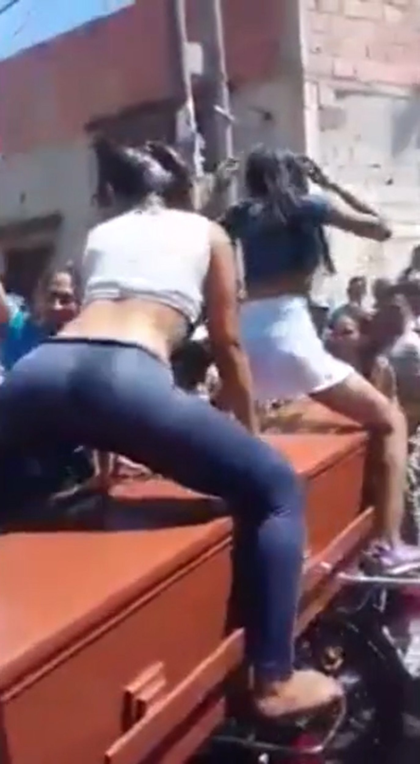 """Pic shows: Another girl joins to dance. Footage of women sexily twerking in wet T-shirts over a coffin have gone viral on social networks in what appears to be a bizarre tribute to their dead friend. The video, posted online on the Facebook page of university student of Memes Universitarios UDC, in the city of Popayan in Colombia has now logged an incredible 19 million hits. The video's origin is unknown although it is thought to have been recorded in Central America or the Caribbean. The video, named """"When Brayan dies"""" shows a brunette woman over a coffin twerking repeatedly while being encouraged by a group of people surrounding the coffin at what appears to be the funeral of Brayan. They can be sleep lifting her skirt up and slapping her bottom. A woman wearing a blue shirt is seen slapping the bottom of the sensual brunette while shouting and she then proceeds to slap the coffin lid. Then another woman is seen getting up over the coffin to also twerk over it. Water is poured over the dancing women, causing their clothes to cling sexily to their bodies. The video went viral on social networks - and caused outrage among viewers. Many criticised what they perceived as a lack of respect for the dead. One man, ëRicky Urgelí, said; """"I cannot believe it, it is the most cynical thing that I have ever seen. It is inhuman, disgusting and it shows a lack of respect"""". Netizen ëPatricia Andrea Cortes Molinaí wrote: """"What a pity seeing girls who could be my daughters moving like bÖ Better not to say what kind of values they have received as they only show the lack of respect by themselves."""" (ends)"""