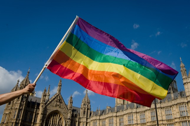 """UK Government isn't planning on making gay conversion therapy illegal (Getty) A protestor holds a rainbow flag outside the Houses of Parliament in central London on June 3, 2013, as protestors gather in support of same-sex marriage. A """"wrecking amendment"""" aimed at derailing the government's same-sex marriage bill, which was passed in the Commons despite the opposition of 133 Tory MPs, is being debated in the House of Lords. AFP PHOTO/Leon Neal (Photo credit should read LEON NEAL/AFP/Getty Images)"""