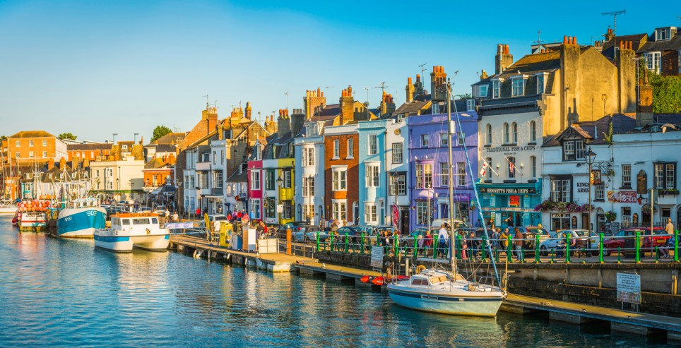 Colourful cottages, fishing boats and yachts around the harbour as holiday makers and locals enjoy the warm summer evening outside waterfront pubs and restaurants at the popular seaside resort town of Weymouth, Dorset.
