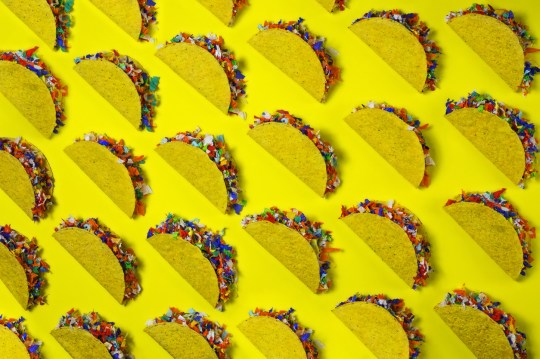Rows of taco shells stuffed with colorful confetti - taco party concept