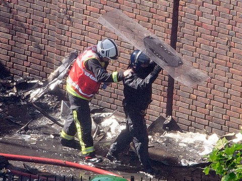 Riot police protect firefighters from falling debris Grenfell tower block fire