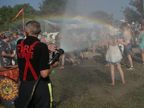 Firefighters douse Glastonbury revellers on the hottest day of the year – and create stunning rainbow effects