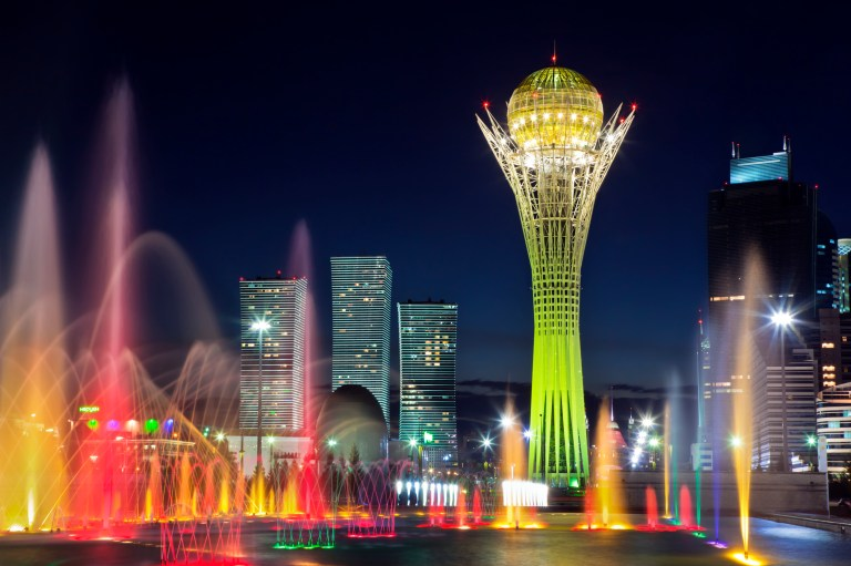 Coloured lights of Song Fountain with Northern Lights skyscrapers and Bayterek Tower along central boulevard (Nurzhol Bulvar) in new city center of Astana at twilight.