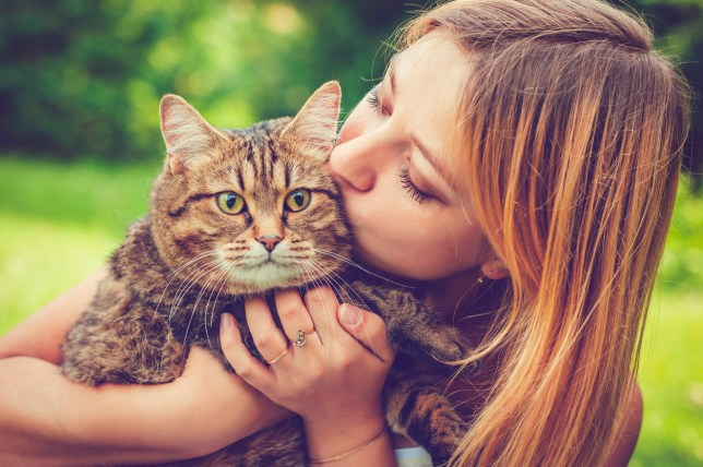 Happy young woman and her cat outdoors in a park in summer