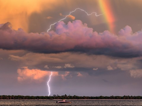 Photographer captures once in a lifetime shot of lightning striking under a rainbow