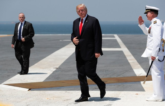 As Ships Captain Rick McCormack salutes at right, President Donald Trump walks to board Marine One on the flight deck of the USS Gerald R. Ford (CVN 78) at Naval Station Norfolk, Va., Saturday, July, 22, 2017, after the commissioning ceremony of the aircraft carrier. (AP Photo/Carolyn Kaster)