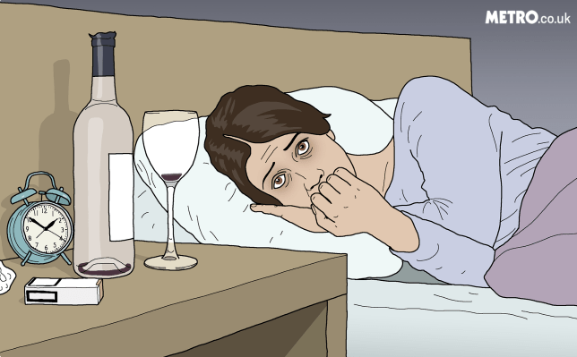 Girl lies worrying in bed with an empty bottle of wine on her bedside table.