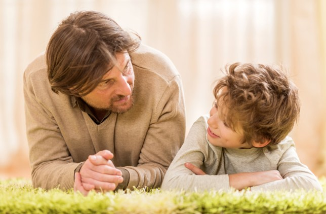 Mid adult father and his little boy lying down on the carpet at home talking to each other.