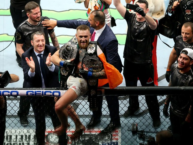 Conor McGregor smiles sitting on the cage with his two belts