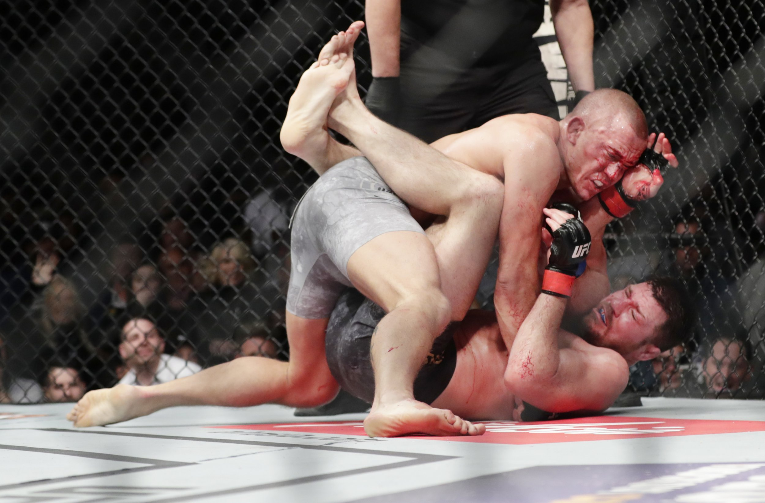 UFC legend Georges St-Pierre chokes out Michael Bisping to claim middleweight title