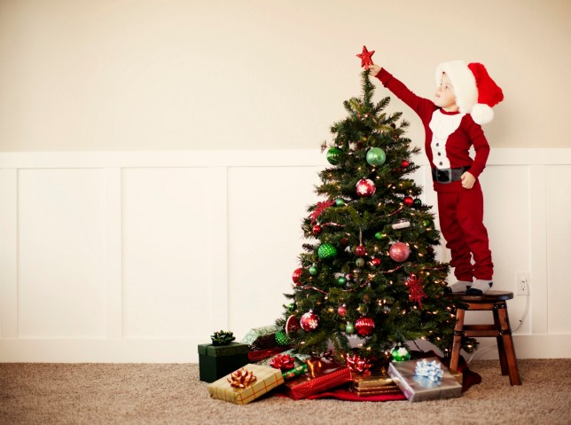 A young boy dressed in Santa pajamas places a star a top the Christmas tree
