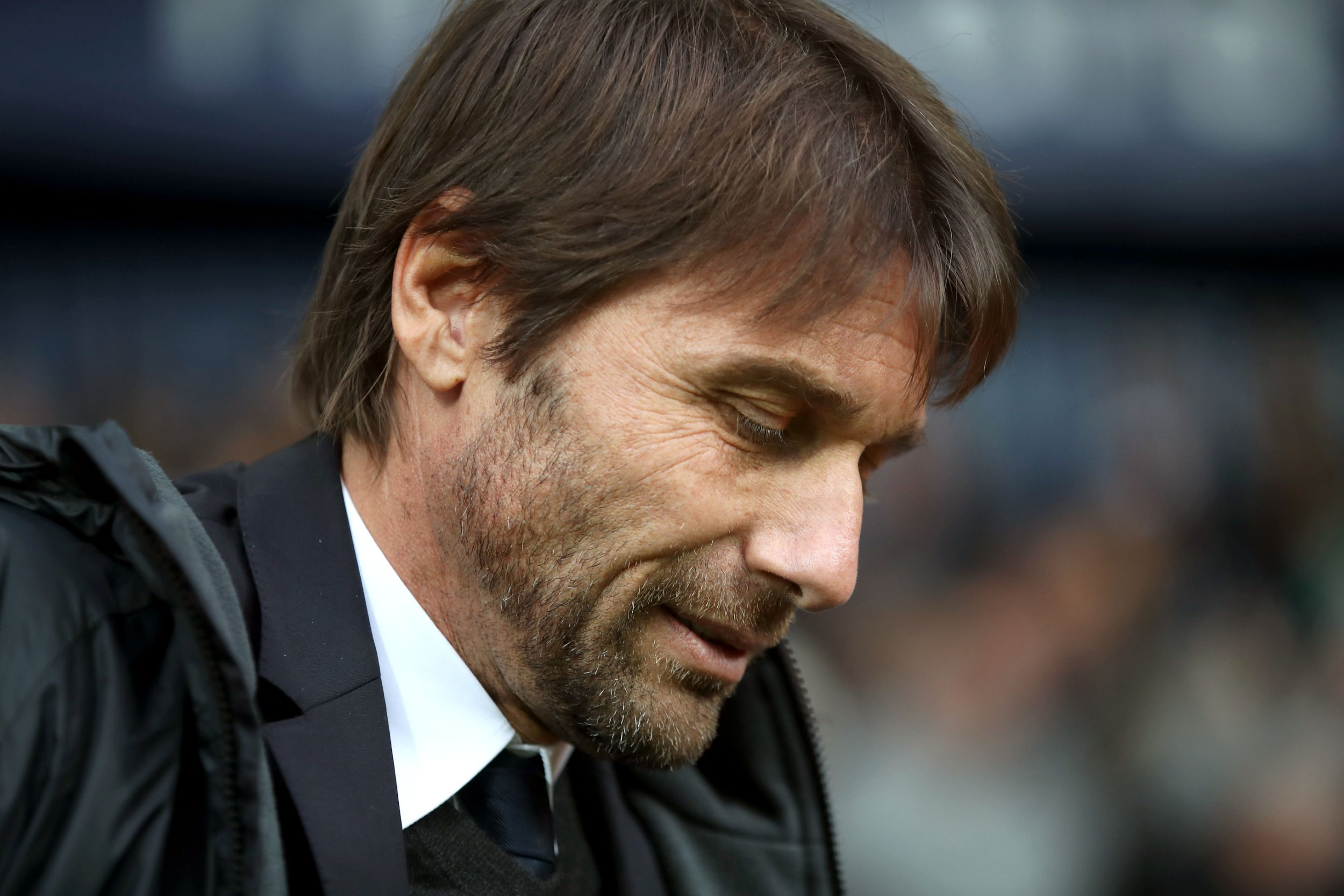 A strained looking Antonio Conte with his head down