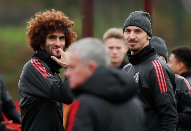 anchester United's Marouane Fellaini and Zlatan Ibrahimovic look at manager Jose Mourinho during training.