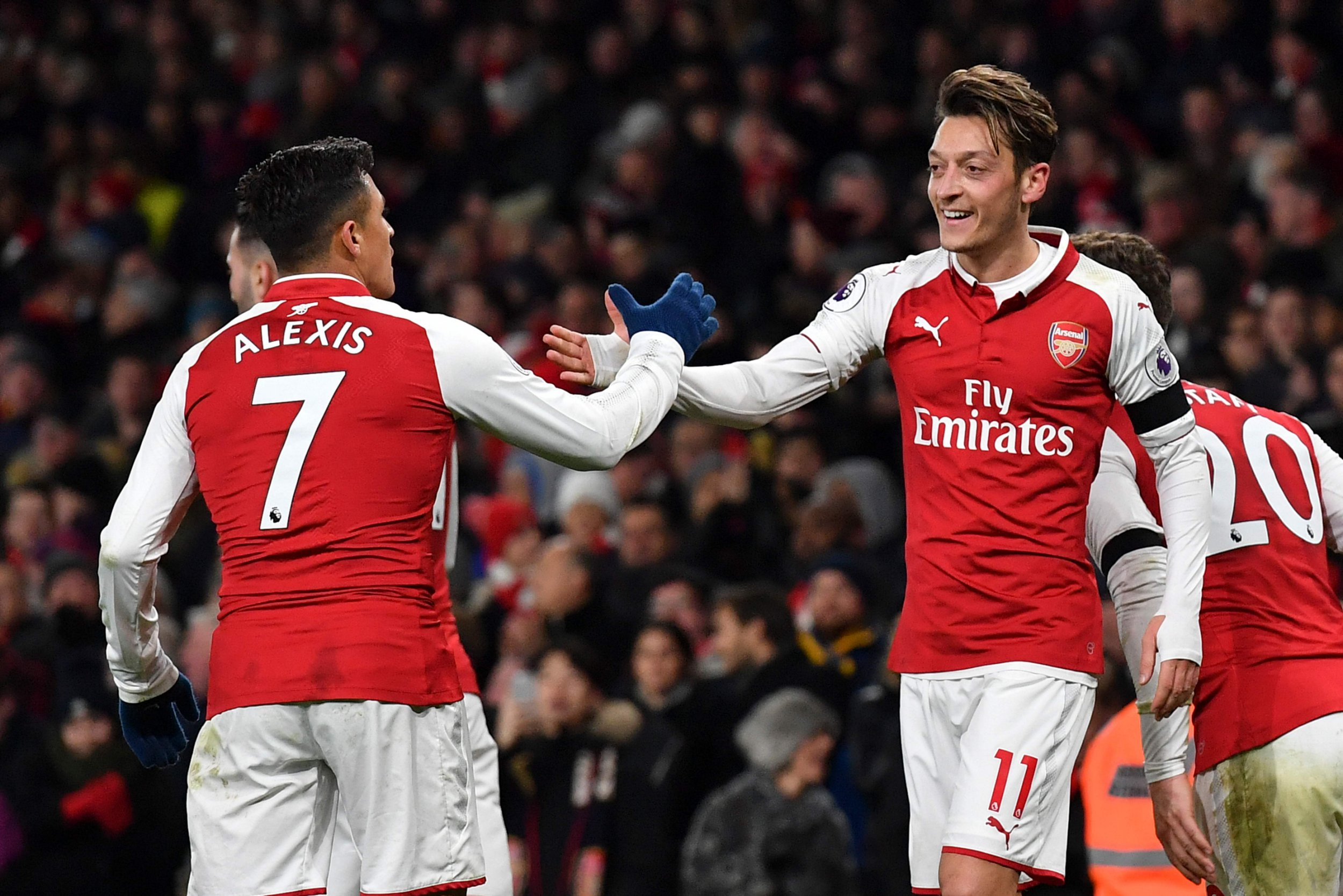 Mesut Ozil high fives with Alexis Sanchez