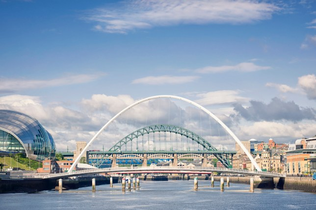 View along the River Tyne showing several bridges connecting Newcastle with Gateshead, with the Gateshead millennium Bridge in the foreground, followed by the Tyne Bridge.