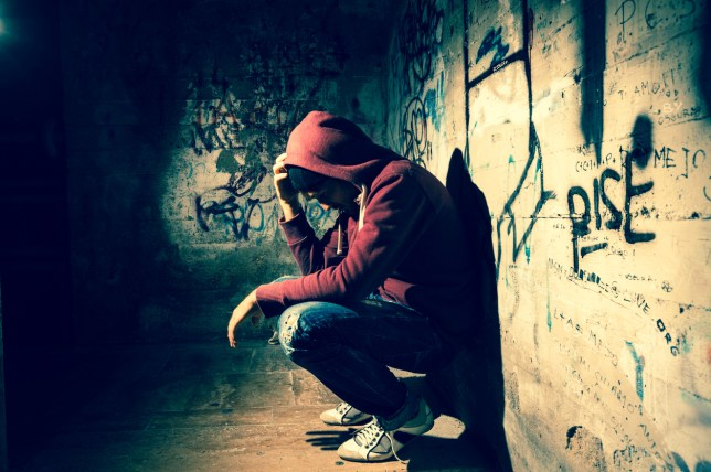 Young man in a hoodie crouched down on the floor by a wall full of graffiti