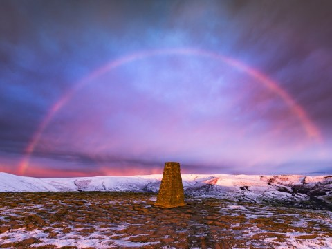 Spectacular rare snowbow pictured at sunrise across the Peak District