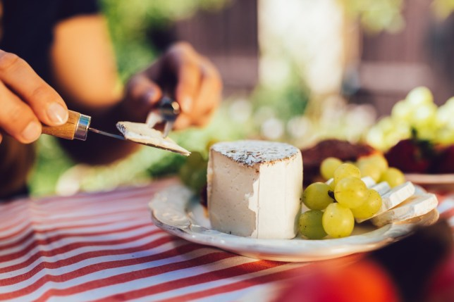 Woman eating rench soft cheese using a special cheese knife